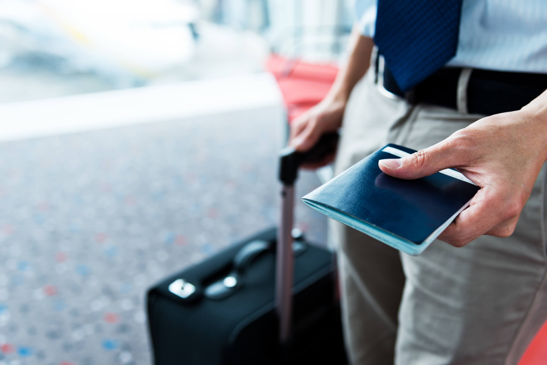 Business person carrying passport and wheeling suitcase
